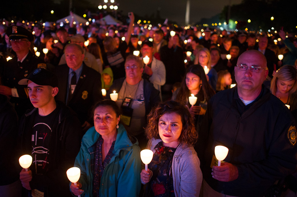 . Family members of police officers killed in the line of duty hold candles during the National Anthem at the start of the National Law Enforcement Officers Memorial Fund 30th annual Candlelight Vigil, to commemorate new names added to the monument, on the Mall in Washington, Sunday, May 13, 2018. (AP Photo/Cliff Owen)