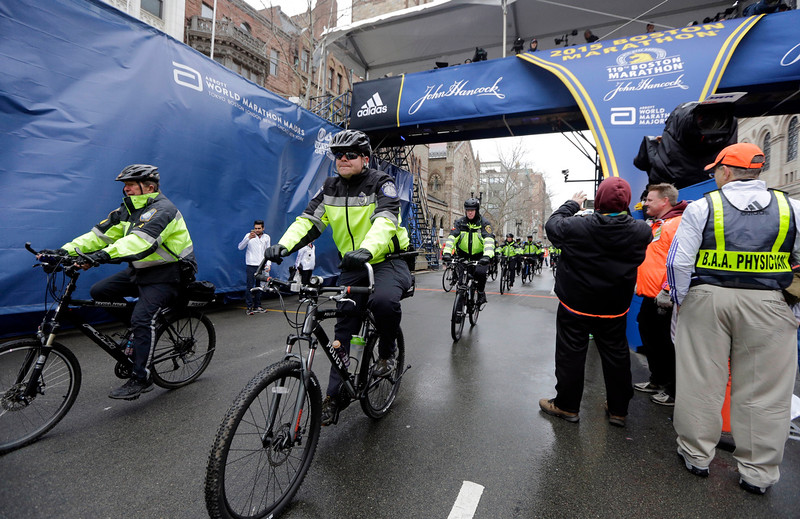 . Police officers patrol near the finish line of the Boston Marathon, Monday, April 20, 2015, in Boston. (AP Photo/Elise Amendola)