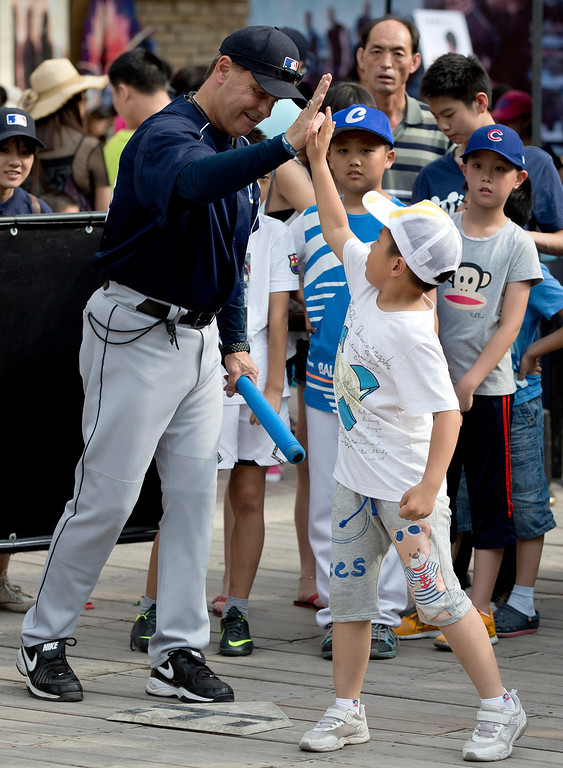 . Rick Dell, director of Baseball Development in Asia for Major League Baseball (MLB), left, cheers a Chinese boy  during an event held at a shopping mall, on International Children\'s Day in Beijing Saturday, June 1, 2013. (AP Photo/Andy Wong)