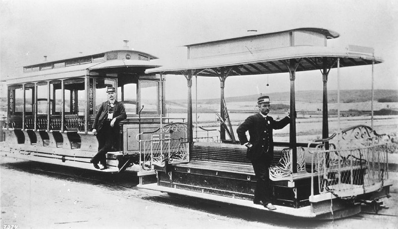 Open-air streetcar with its trailer and two operators on west Seventh Street looking north from Alvarado Street, ca.1890
