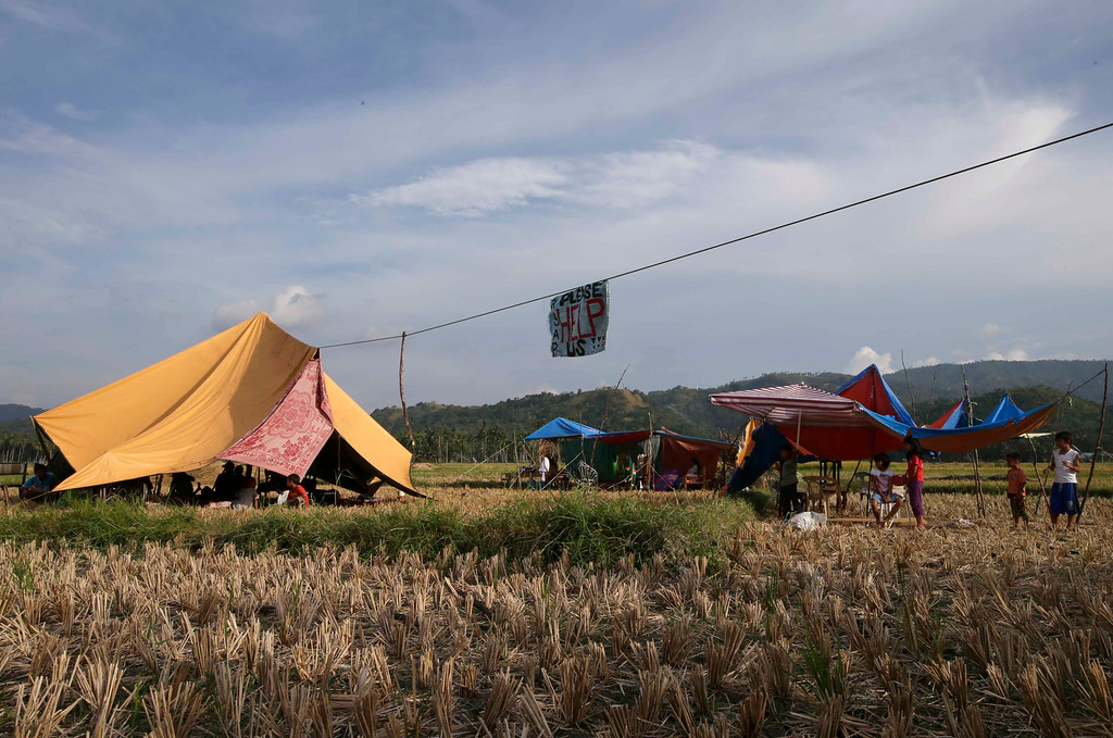 """. People display a message \""""Please Help Us\"""" as they camp out in the middle of a rice field to avoid aftershocks at Calape township, Bohol province in central Philippines, Wednesday Oct. 16, 2013. (AP Photo/Bullit Marquez)"""