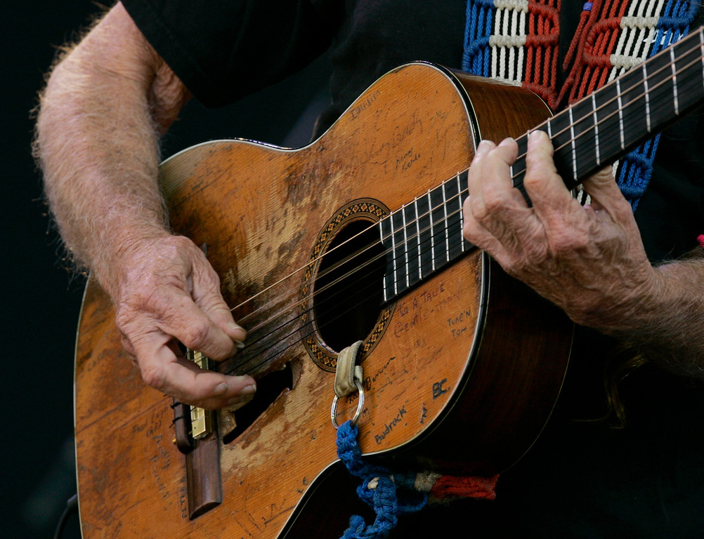 . Willie Nelson\'s guitar shows decades of wear as he  performs at the Crossroads Guitar Festival in Chicago, Saturday, July 28, 2007. (AP Photo/Charles Rex Arbogast)