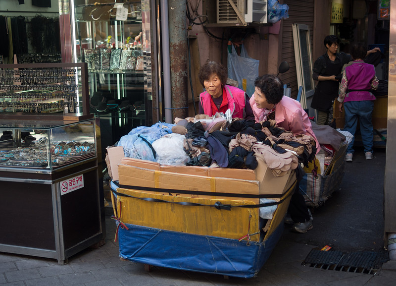 Pushing their cart of stockings at Namdaemun market.