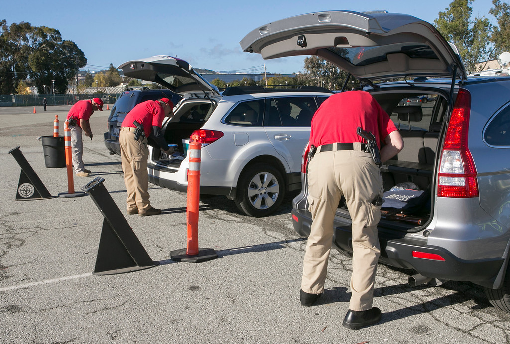 . Sheriff deputies remove guns from vehicles that were turned in during an anonymous gun buyback at the San Mateo County Event Center. (John Green/Staff)