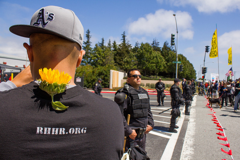 A participant wearing the signature sunflower in the march against the Chevron Oil Refinery stands opposite a line of police in front of the factory's gates in Richmond, California August 3, 2013.