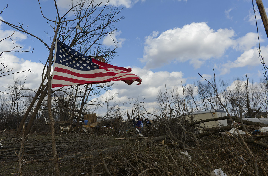 . A flag flies on a tree along Fowler Road outside of Flagg Center, Ill., on Friday, April 10, 2015.  A tornado hit the town of Fairdale, Ill., Thursday night killing two people. The National Weather Service says at least two tornadoes churned through six north-central Illinois counties. (AP Photo/Matt Marton)