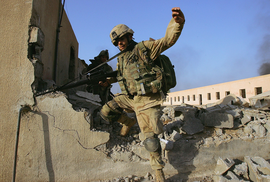 . U.S. Army 1st Infantry Division\'s 2nd Battalion-2nd Regiment Specialist Josh Harrill from Greenbay , Wisconsin leaps through an opening in a broken wall while clearing abandoned buildings of insurgent fighters November 10, 2004 during fighting in the Iraqi insurgent stronghold of Fallujah.  (Photo by Scott Nelson/Getty Images)