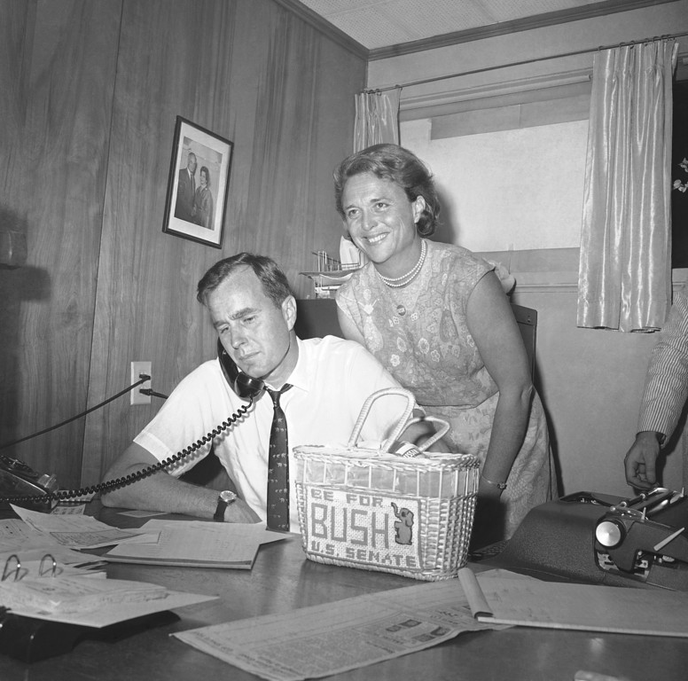 . George Bush, candidate for the Republican nomination for the U.S. Senate, gets returns by phone at his headquarters in Houston, Saturday, June 6, 1964 as his wife Barbara, beams her pleasure at the news. Bush was leading his opponent Jack Cox in the run-off primary. Bush will face Sen. Ralph Yarborough (D-Tex) in the November general election if his lead holds and he is the winner. (AP Photo/Ed Kolenovsky)