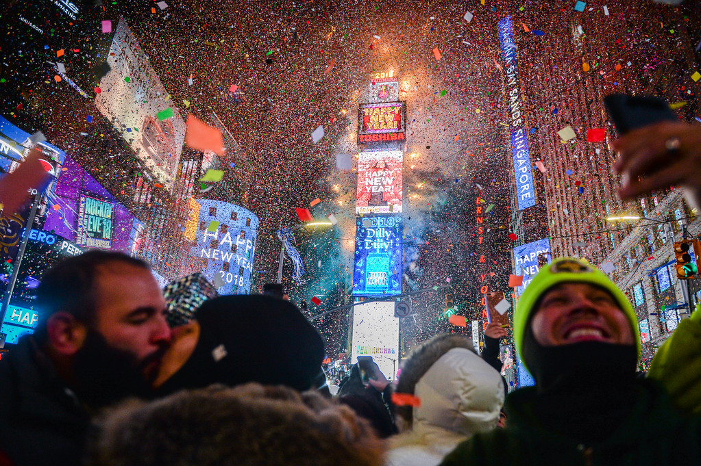 . People celebrate New Year as confetti fall down after the countdown to midnight in Times Square during New Year\'s celebrations, Monday, Jan. 1, 2018, in New York. (AP Photo/Go Nakamura)