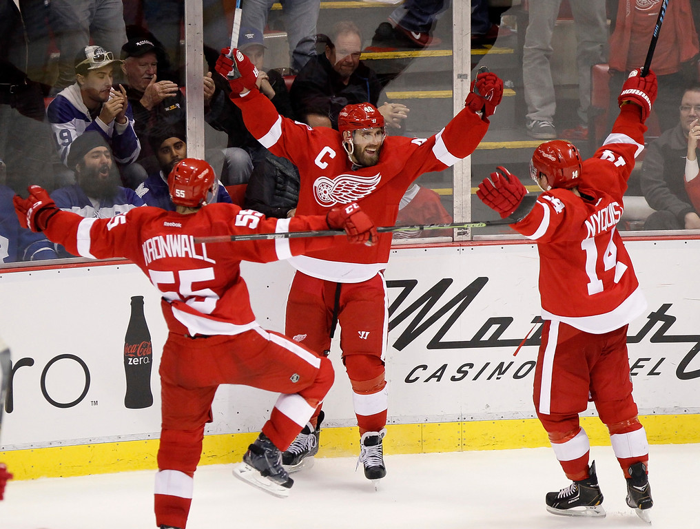 . Detroit Red Wings\' Henrik Zetterberg, center, celebrates with teammates Niklas Kronwall (55) and Gustav Nyquist (14), all of Sweden, after his overtime goal that defeated the Toronto Maples Leafs 1-0 during an NHL hockey game Saturday, Oct. 18, 2014, in Detroit. (AP Photo/Duane Burleson)