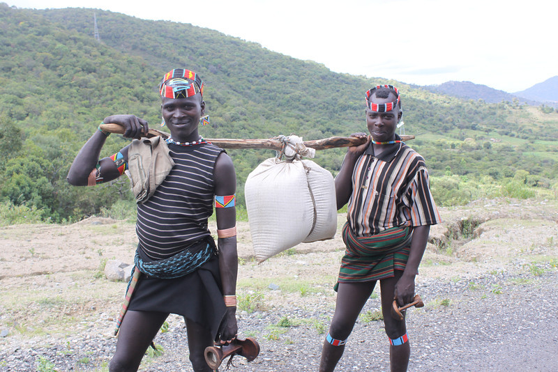 Two Bena tribe boys with teff (used to make injera) on a stick