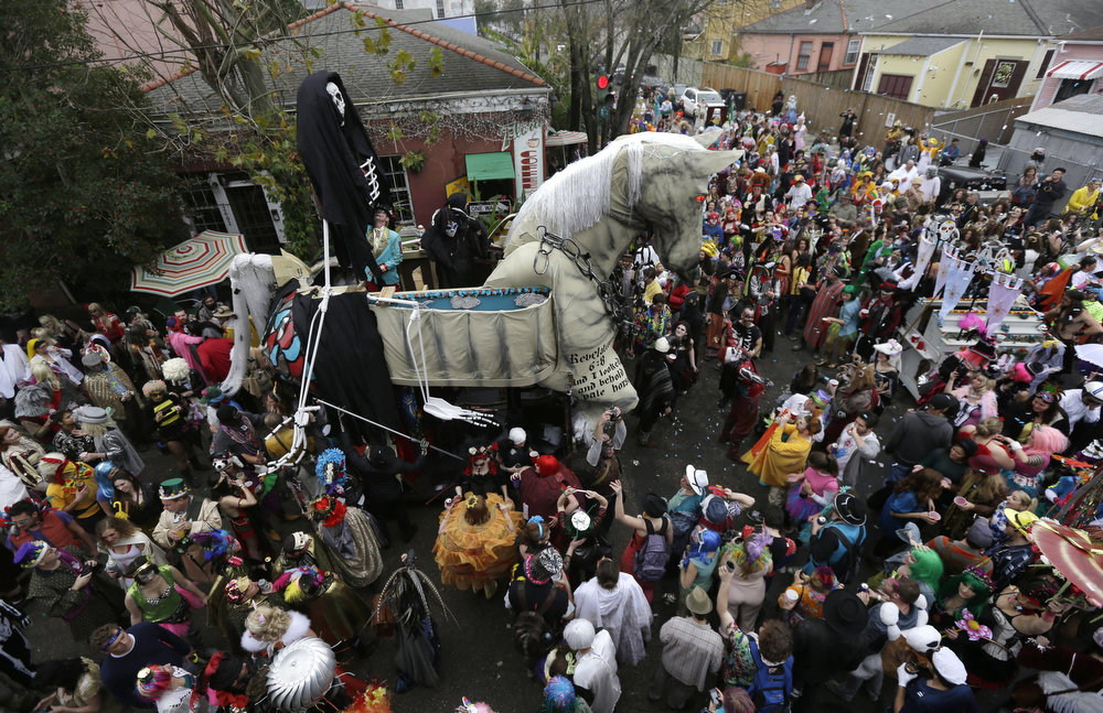 Description of . A trojan horse float makes its way through the crowd as revelers gather for the start of the Society of Saint Anne walking parade in the Bywater section of New Orleans during Mardi Gras day, Tuesday, Feb. 12, 2013.  Overcast skies and the threat of rain couldn't dampen the revelry of Mardi Gras as parades took to the streets, showering costumed merrymakers with trinkets of all kinds.  (AP Photo/Gerald Herbert)