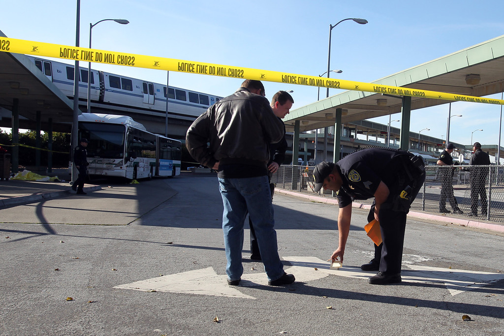 . A dead body covered, far left, lies on the sidewalk next to an AC Transit bus  as police investigate the fatal shooting in the bus yard outside the Bay Fair BART  station in San Leandro, Calif., on Saturday, Jan. 19, 2013. (Ray Chavez/Staff)