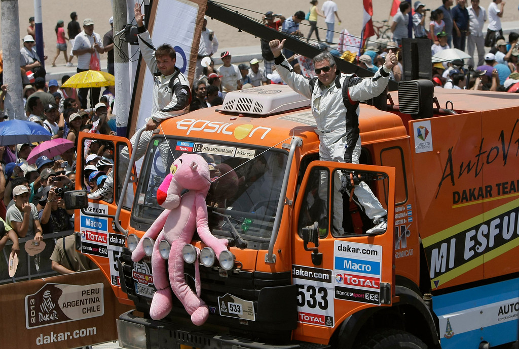 . Mercedes driver Walter D\'Angostini, right, and co-driver Hernan D\'Angostini, both from the Argentina, wave from their vehicle during the symbolic start of the Peru-Argentina-Chile Dakar Rally 2013 in Lima, Peru, Saturday, Jan. 5, 2013. The race of over 400 vehicles including cars, bikes, trucks and quads begins Saturday in Lima and finishes in Santiago, Chile on Jan. 20. (AP Photo/Karel Navarro)