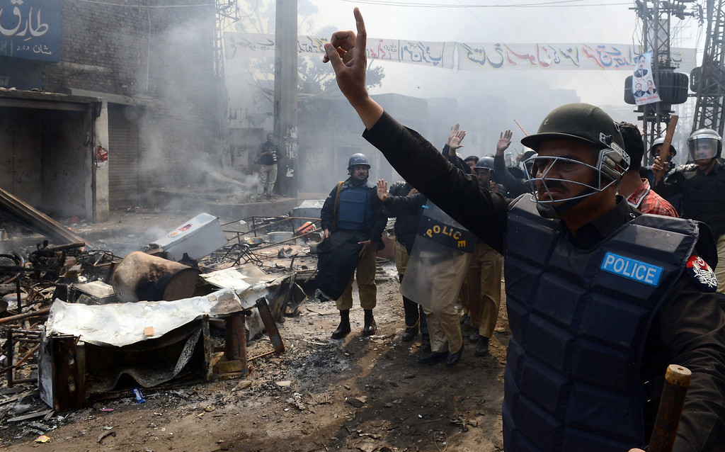 . Pakistani riot police gesture during a protest by Muslim demonstrators over alleged blasphemous remarks by a Christian in a Christian neighborhood in Badami Bagh area of Lahore on March 9, 2013. Thousands of angry protestors on March 9 set ablaze more than 100 houses of Pakistani Christians over a blasphemy row in the eastern city of Lahore, officials said. Over 3,000 Muslim protestors turned violent over derogatory remarks allegedly made by a young Christian, Sawan Masih, 28 against Prophet Muhammad in a Christian neighboorhood in Badami Bagh area. Arif Ali/AFP/Getty Images