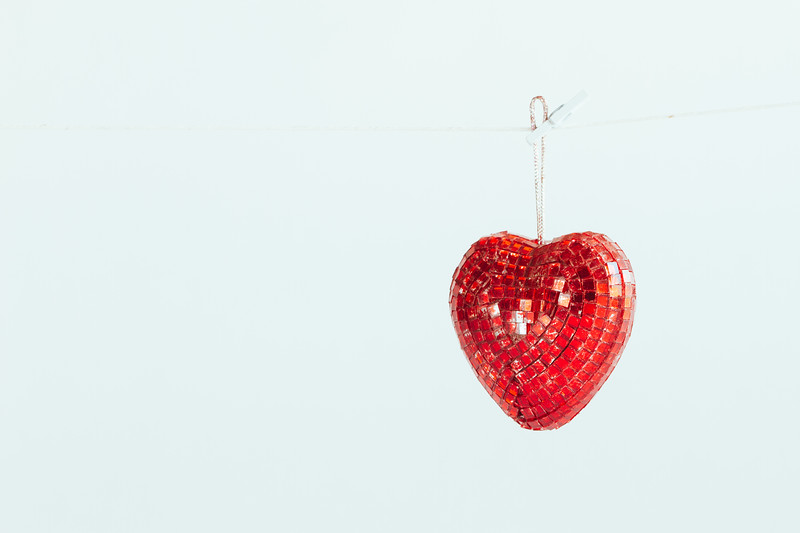 Red heart ornament hanging on a line, held by a clothespin, isolated on a light background