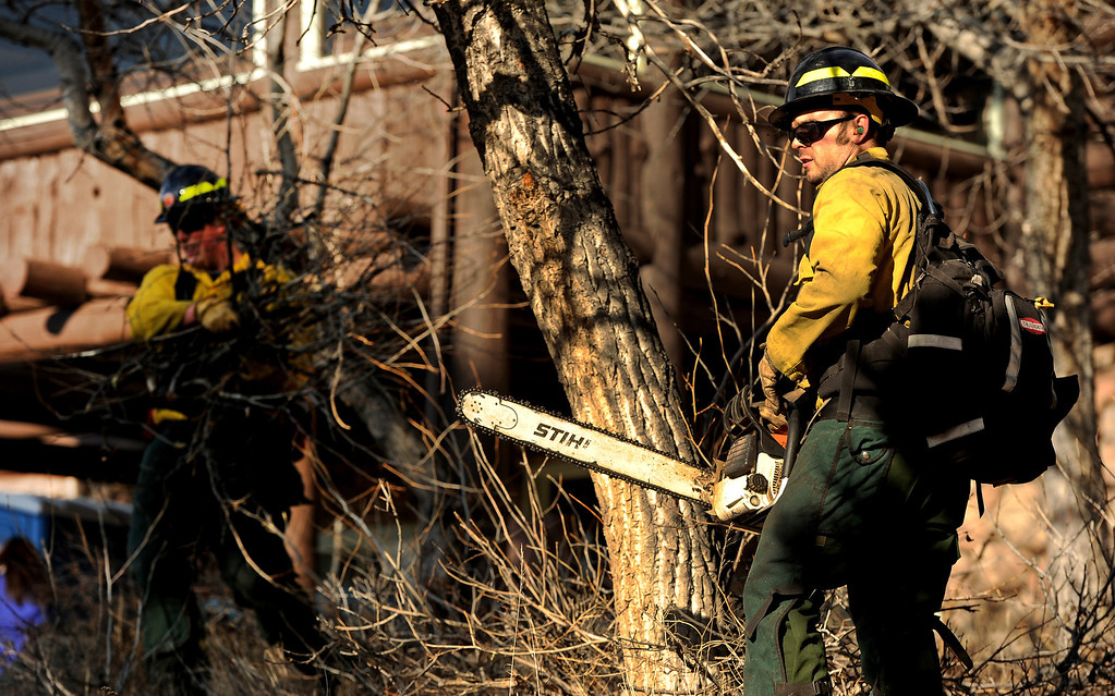 . Wildland firefighters Chris Wetzel, left and Mitch Sprague, right,  from Lafayette Fire,  clear brush and debris from the Moraine Park Vistor\'s Center to protect the structure just in case the fire reaches the building on December 2nd, 2012.