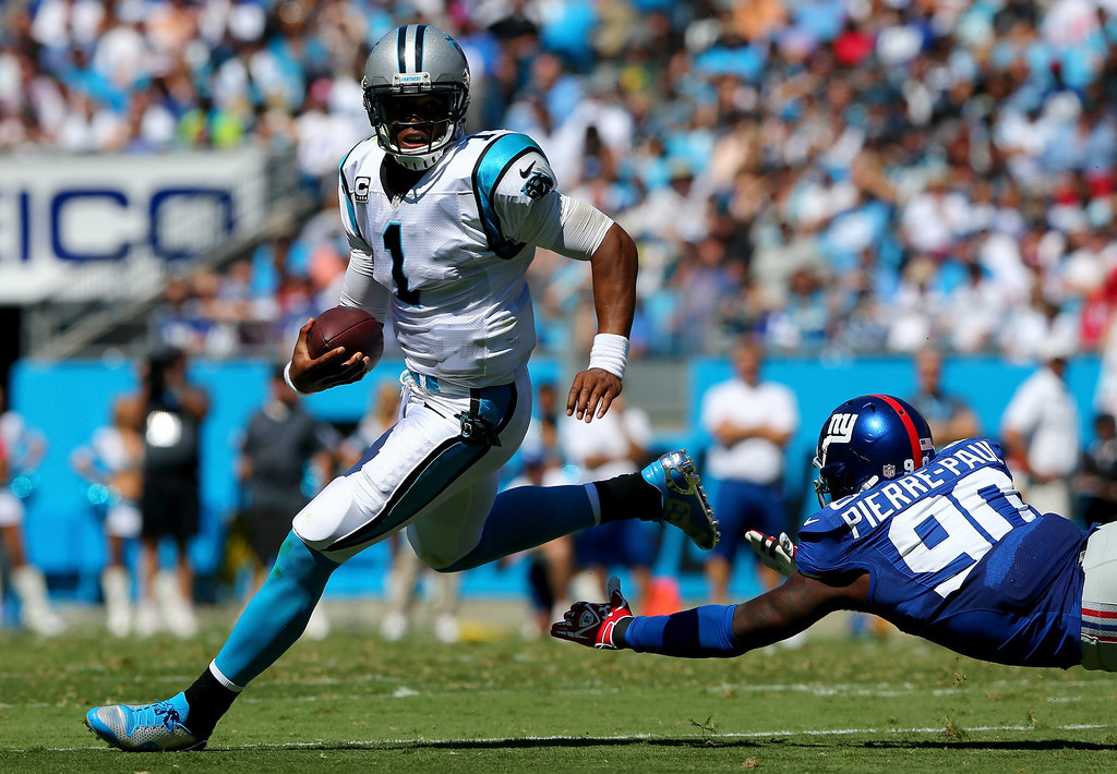 . Cam Newton #1 of the Carolina Panthers runs away from  Jason Pierre-Paul #90 of the New York Giants during their game at Bank of America Stadium on September 22, 2013 in Charlotte, North Carolina.  (Photo by Streeter Lecka/Getty Images)
