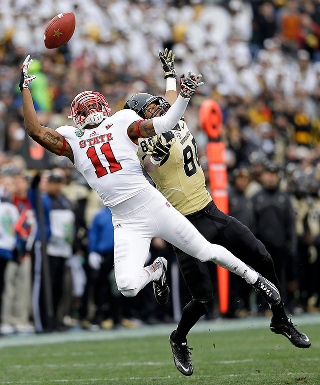 . North Carolina State defensive back Juston Burris (11) breaks up a pass intended for Vanderbilt wide receiver Chris Boyd (80) in the second quarter of the Music City Bowl NCAA college football game on Monday, Dec. 31, 2012, in Nashville, Tenn. (AP Photo/Mark Humphrey)