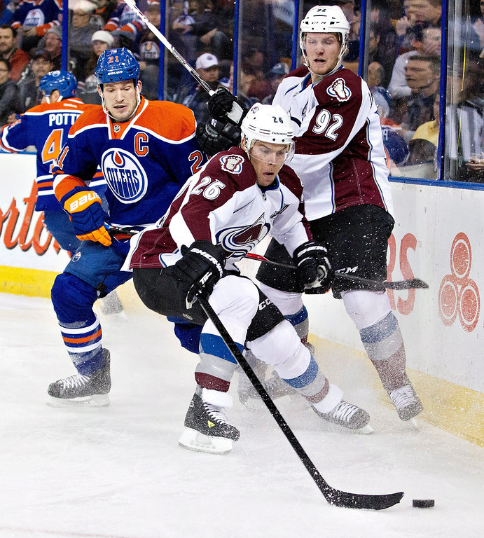 . Colorado Avalanche\'s Paul Stastny (26) and Gabriel Landeskog (92) battle for the puck with Edmonton Oilers\' Andrew Ference (21) during first-period NHL hockey game action in Edmonton, Alberta, Thursday, Dec. 5, 2013. (AP Photo/The Canadian Press, Jason Franson)