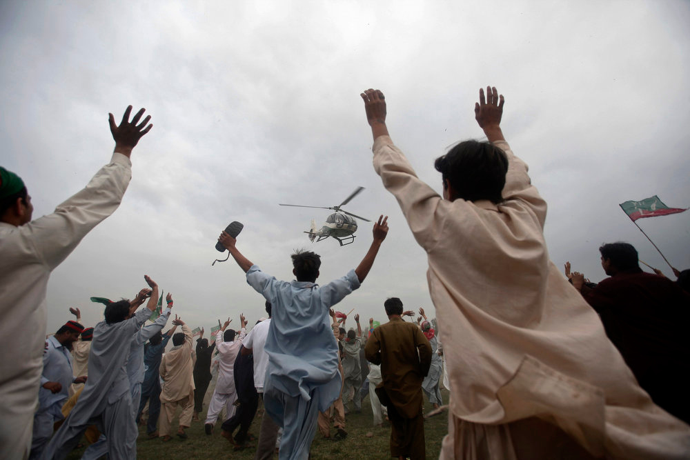 . Supporters wave towards a helicopter transporting Pakistan Tehreek-e-Insaf\'s (PTI) Chief Imran Khan as he leaves after his election campaign rally in Nowshera, Khyber Pakhtunkhwa province May 4, 2013. Pakistan\'s general elections will take place on May 11. REUTERS/Fayaz Aziz
