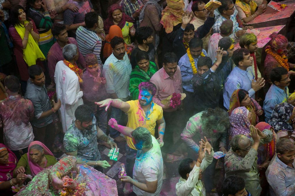 . Hindu devotees throw colored powders on each other inside Banke Bihari temple, dedicated to Lord Krishna, during Holi festival celebrations in Vrindavan, India, Wednesday, March 8, 2017. Holi, the festival of colors, celebrates the arrival of spring. (AP Photo/Manish Swarup)