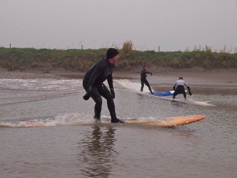 Steve with other surfers riding the Severn bore. Dave in distance.