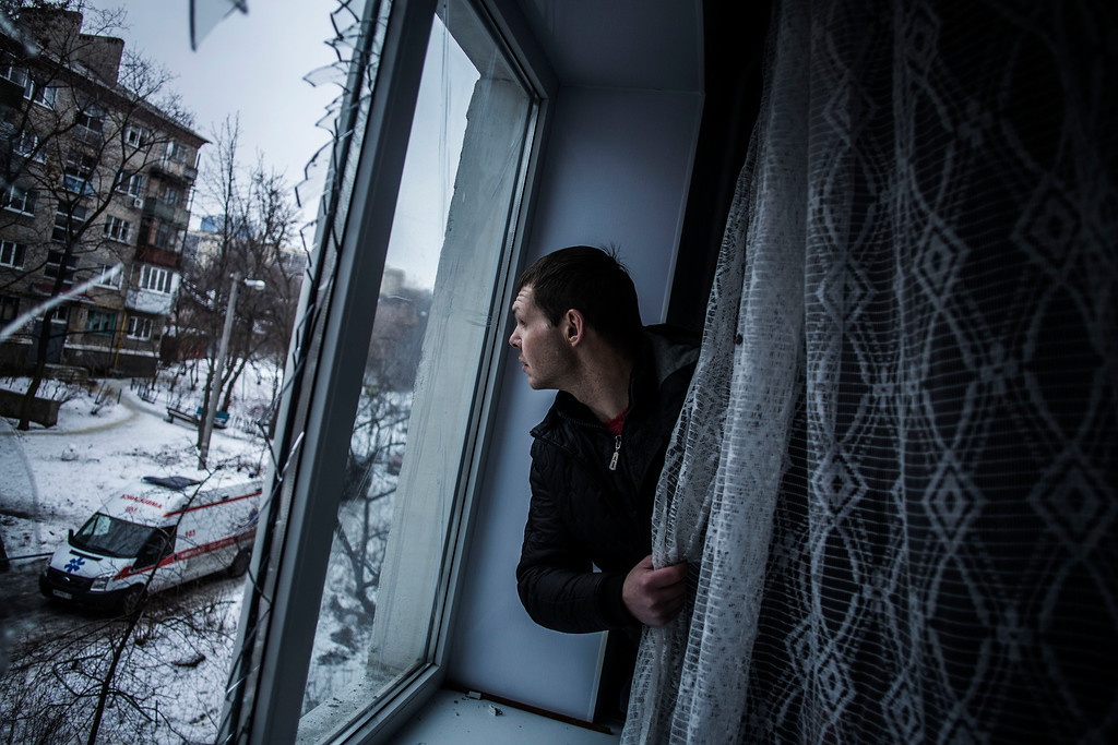 . Alexander, 35, looks through a broken window of his flat, hit by Ukrainian Army Artillery, in the Voroshilovsky area, center of Donetsk, Ukraine. Sunday, Jan. 18, 2015. The separatist stronghold, Donetsk, was shaken by intense outgoing and incoming artillery fire as a bitter battle raged for control over the city\'s airport. Streets in the city, which was home to 1 million people before unrest erupted in spring, were completely deserted and the windows of apartments in the center rattled from incessant rocket and mortar fire. (AP Photo/Manu Brabo)