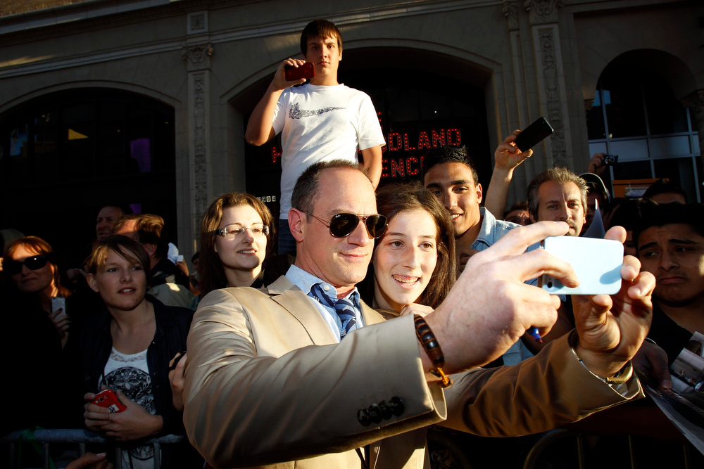 ". Cast member Christopher Meloni poses with a fan at the premiere of ""42\"" in Hollywood, California April 9, 2013. The movie opens in the U.S. on April 12.  REUTERS/Mario Anzuoni"