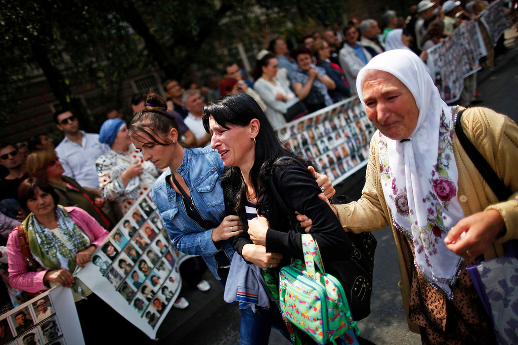 . Bosnian women cry while watching a truck, one of three carrying 409 coffins of newly identified victims of the 1995 Srebrenica massacre, in front of the presidential building in Sarajevo July 9, 2013. The bodies of the recently identified victims will be transported to the memorial centre in Potocari where they will be buried on July 11 marking the 18th anniversary of the massacre in which Bosnian Serb forces commanded by Ratko Mladic killed up to 8,000 Muslim men and boys and buried them in mass graves. REUTERS/Dado Ruvic