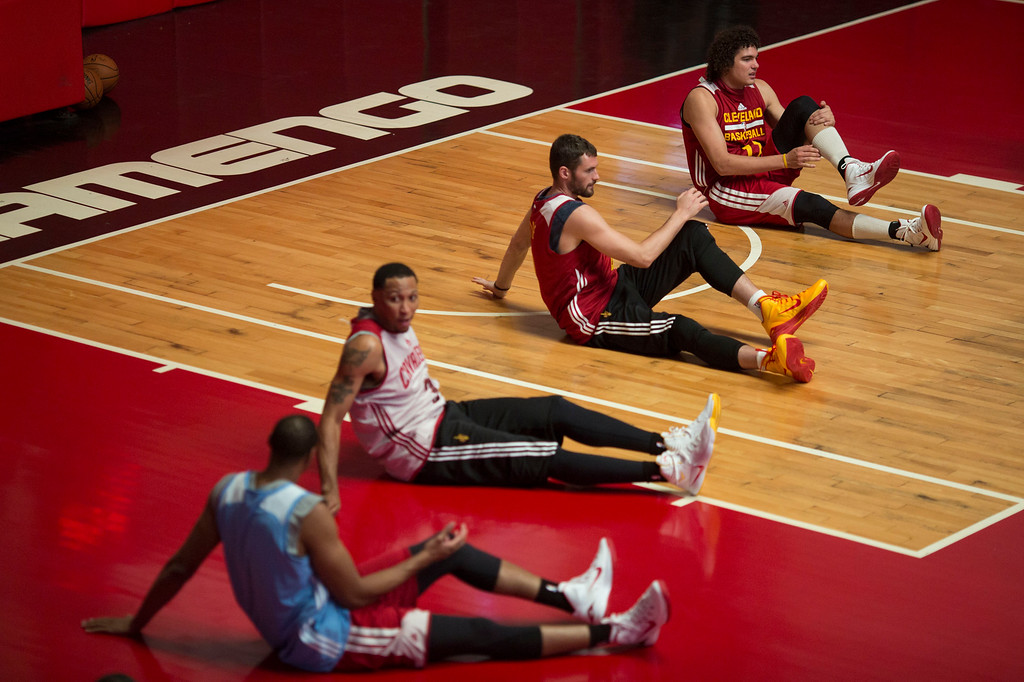 . Cleveland Cavaliers\' Anderson Varejao, top, stretches with teammates during a training session in Rio de Janeiro, Brazil, Thursday, Oct. 9, 2014. The Cleveland Cavaliers will play the Miami Heat in a preseason game in Rio, on Saturday, as part of the NBA Global Games. (AP Photo/Felipe Dana)