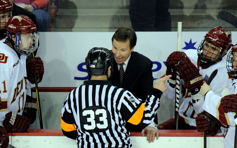 . Referee Brad Shepherd (33) explains about a penalty to University of Denver head coach George Gwozdecky in the second period of the game against North Dakota at Magness Arena in Denver, CO. on Saturday, February 25, 2012. Hyoung Chang, The Denver Post