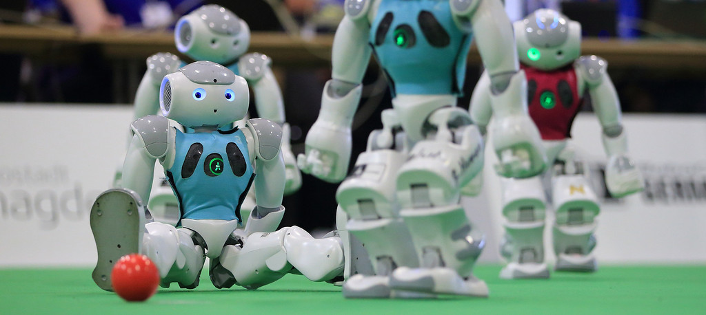 ". Robots of the German city of Bremen team ""B-Human\"" play versus team \""MRL\"" of Iranian university Qazvin Azad in a match of the category \""Standard Platform Ligue\"" during the \""RoboCup German Open 2014\"" in Magdeburg, eastern Germany on April 3, 2014. 950 participants from 12 countries participate in the three-day tournament. The robots are required to master a variety of disciplines, including communication, soccer, rescue and dance.  AFP PHOTO / DPA/ JENS WOLF /AFP/Getty Images"