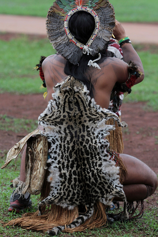 . In this Tuesday, Oct. 1, 2013 photo, a Pataxo Indian wearing a wild cat pelt participates in the first day of the National Indigenous Mobilization in Brasilia, Brazil, where hundreds of people set up camp in front of Congress to oppose a constitutional change that would let lawmakers participate in the demarcation of territories. Indigenous people and their supporters say the proposal would allow agricultural interests to encroach on their lands. (AP Photo/Eraldo Peres)