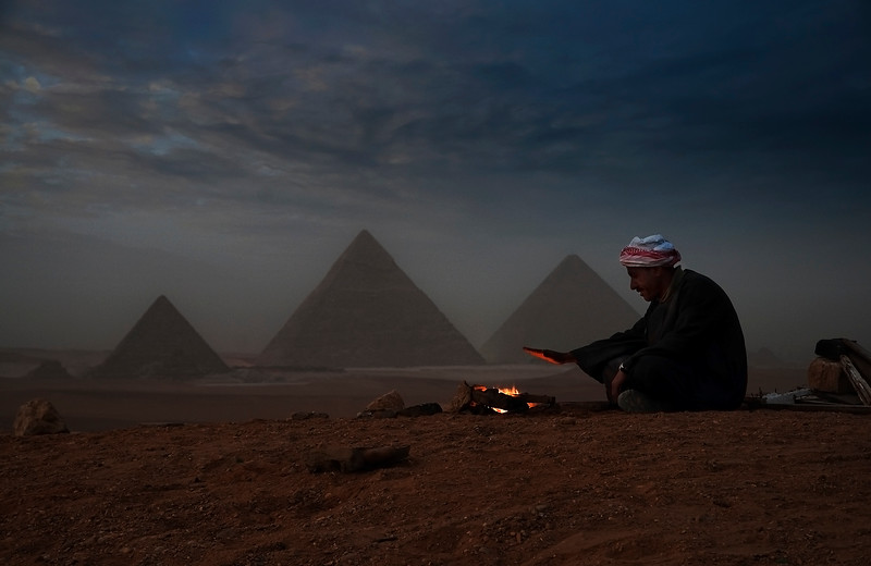 A local guide warms his hands in a cold desert night. The Pyramids of Giza in the background.  Cairo, Egypt, 2010