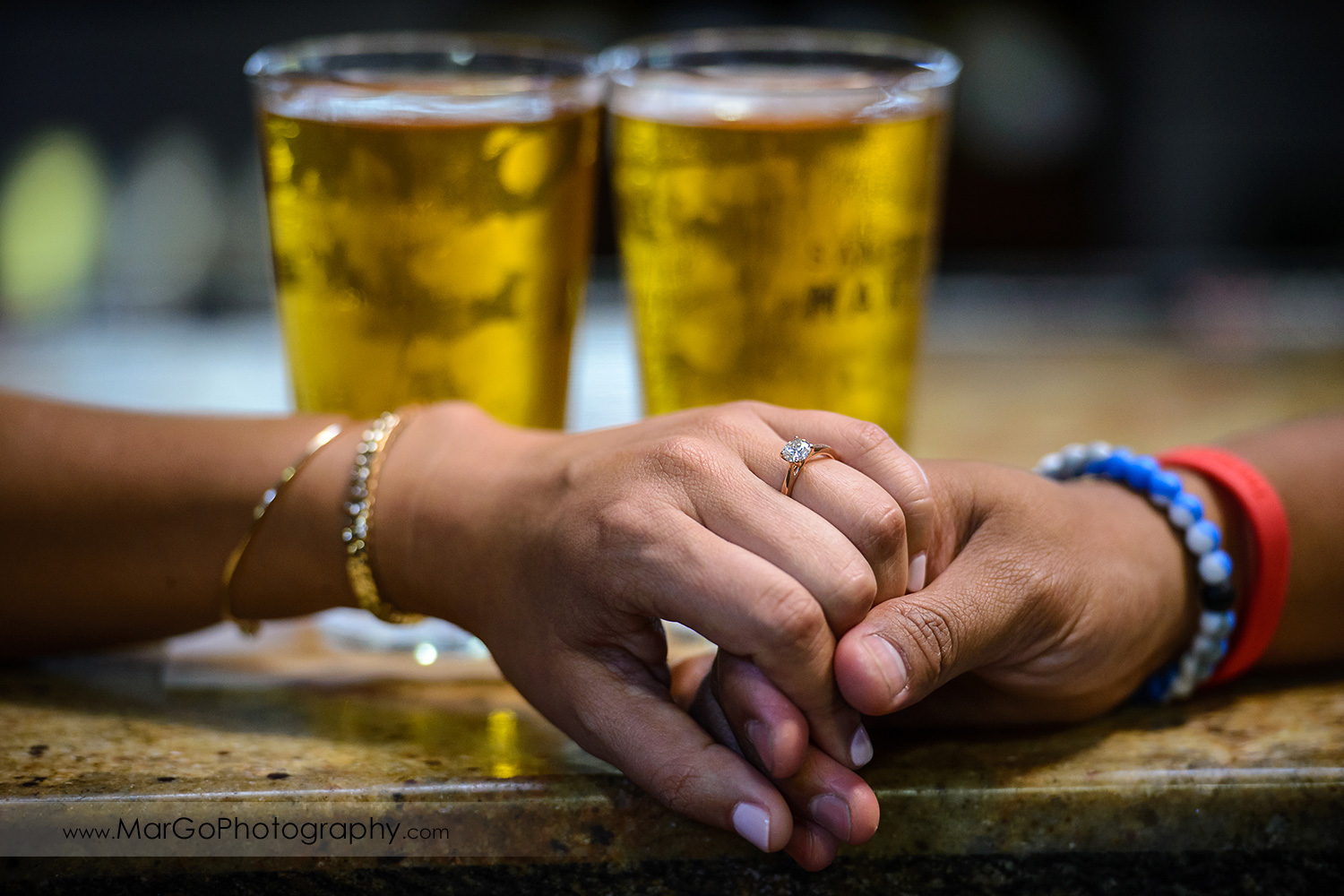 close-up men's hand holding woman's hand with the engagement ring and two beers in the background at San Pedro Square Market in San Jose