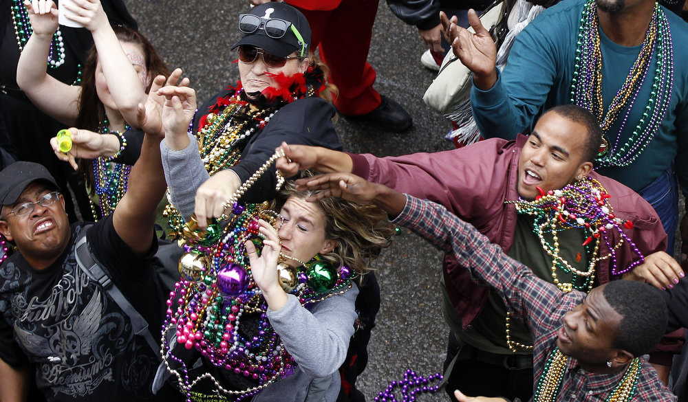 Description of . Revelers grab for beads as they are tossed from the balcony of the Royal Sonesta Hotel on Bourbon Street during Mardi Gras in New Orleans, Tuesday, Feb. 12, 2013. Despite threatening skies, the Mardi Gras party carried on as thousands of costumed revelers cheered glitzy floats with make-believe monarchs in an all-out bash before Lent.   Crowds were a little smaller than recent years, perhaps influenced by the forecast of rain. Still, parades went off as scheduled even as a fog settled over the riverfront and downtown areas.  (AP Photo/Gerald Herbert)