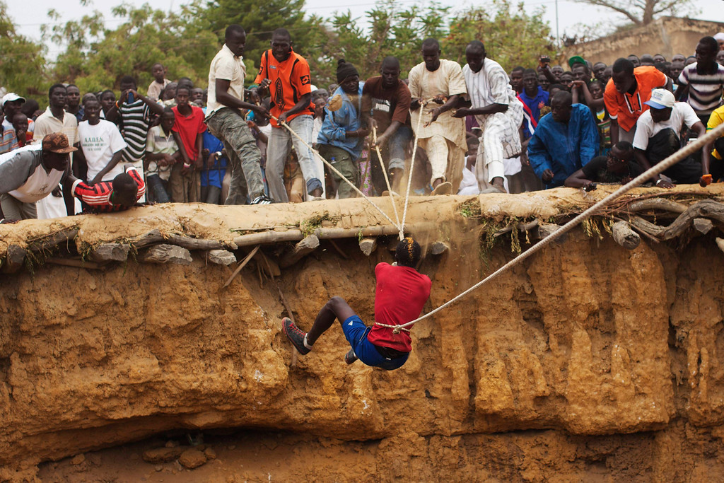 . A man ascends by bungee cords from a large former well during a traditional ceremony in the village of Ndande, May 19, 2013. Every year, inhabitants of the village take part in a Sufi Muslim ceremony called Gamou-Ndande. The ceremony combines nights of praying and chanting as well as traditionally animist ceremonies. The well, called Kalom, was the site of historic battles in Senegalese history. According to local historian Baye Niass, the well dates back to the 16th century. Today there is no water in the former well and it is used for ceremonial purposes. Niass says the well measure 36 meters in depth an 11m in diameter. Picture taken May 19, 2013.  REUTERS/Joe Penney