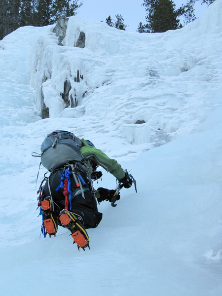An ice climber claims a frozen waterfall