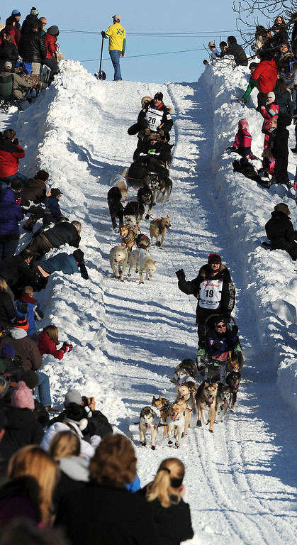 . Scott Janssen of Anchorage, Alaska, top, catches up to Allen Moore of Two Rivers, Alaska, on the Cordova Street hill during the ceremonial start for the 2014 Iditarod Trail Sled Dog Race on Saturday, March 1, 2014, in Anchorage, Alaska. (AP Photo/The Anchorage Daily News, Erik Hill)