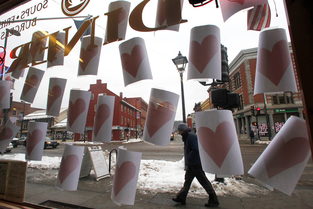 ". Paper hearts hang on a window on Valentine\'s Day on Thursday, Feb. 14, 2013 in Montpelier, Vt. The annual tradition of plastering Montpelier\'s downtown with valentine hearts has happened again.  A person  who is called the ""Valentine\'s Phantom\"" has been putting up the hearts for over 10 years.  (AP Photo/Toby Talbot)"