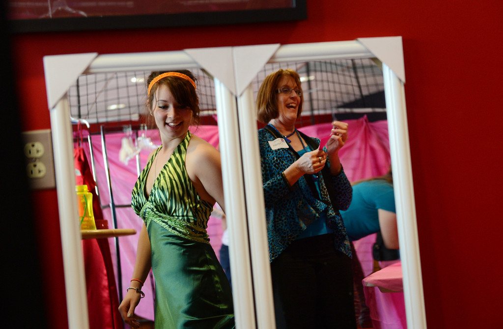 """. COMMERCE CITY, CO. - MARCH 16:  Raven Gereaux, a senior at Legacy High School, admires her dress while having alterations made by Susan Nixon, right, during the Prom Dress Exchange Corp. event in Commerce City, CO March 16, 2013. For the third year, the organization offered teens an opportunity to find a dress for the big night. Gereaux said, Prom is so expensive already, I think it\'s a great opportunity for girls to get a really nice dress for a reasonable price.\"""" With a valid student ID and a suggested $10 donation, teenage girls could chose from 1,356 donated dresses that lined a long hallway at Dick�s Sporting Goods Park.  (Photo By Craig F. Walker/The Denver Post)"""