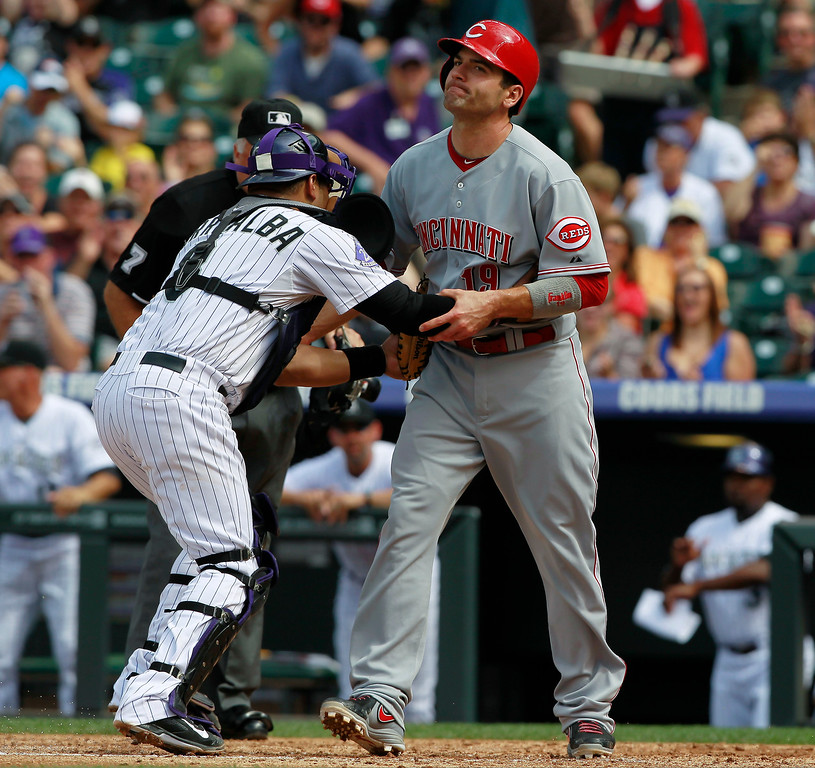 . Colorado Rockies catcher Yorvit Torrealba, left, tags out Cincinnati Reds\' Joey Votto at home plate as Votto was trying to score on an ground ball hit by Chris Heisey in the third inning of a baseball game in Denver, Sunday, Sept. 1, 2013. (AP Photo/David Zalubowski)