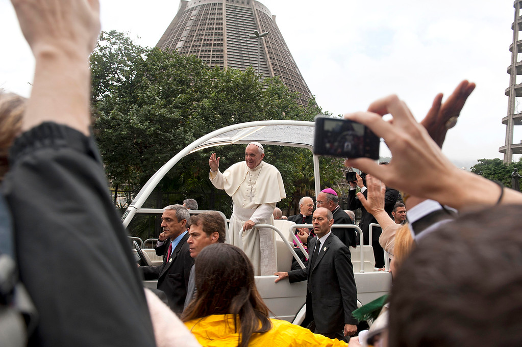 . Pope Francis waves to people from his popemobile in Rio de Janeiro, Brazil, Saturday, July 27, 2013. Pope Francis on Saturday challenged bishops from around the world to get out of their churches and preach, and to have the courage to go to the farthest margins of society to find the faithful. (AP Photo/Nicolas Tanner)