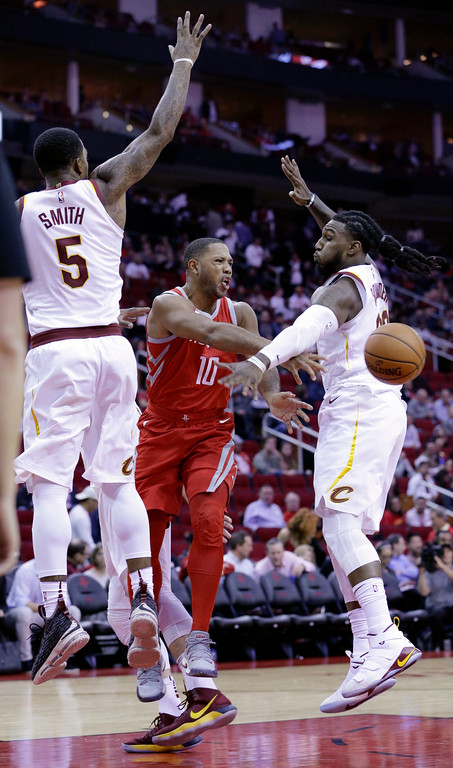 . Houston Rockets guard Eric Gordon (10) passes the ball between Cleveland Cavaliers guard JR Smith (5) and forward Jae Crowder (99) during the second half of an NBA basketball game Thursday, Nov. 9, 2017, in Houston. (AP Photo/Michael Wyke)