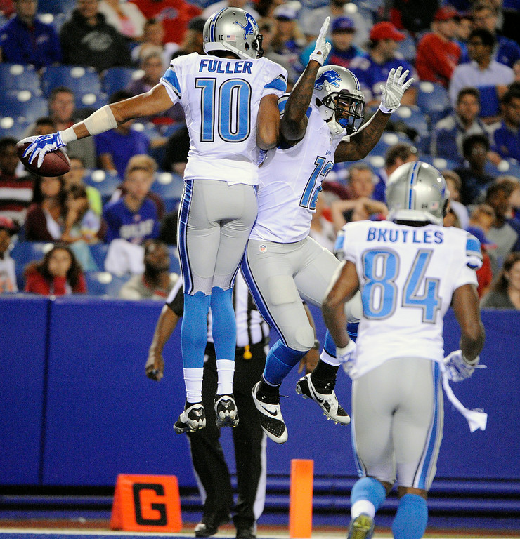 . Detroit Lions wide receiver Corey Fuller (10) and wide receiver Jeremy Ross (12) celebrate a touchdown catch by Fuller on a pass from quarterback Kellen Moore during the first half of a preseason NFL football game against the Buffalo Bills, Thursday, Aug. 28, 2014, in Orchard Park, N.Y. Wide receiver Ryan Broyles (84) looks on during the celebration. (AP Photo/Gary Wiepert)
