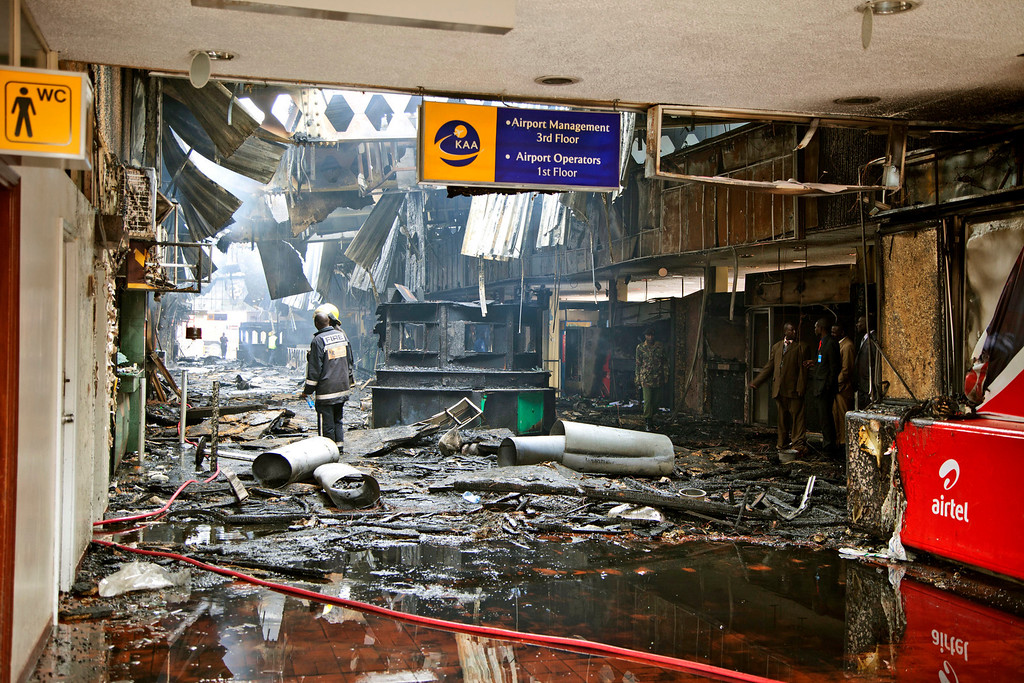 . Firefighters and airport officials view the damage caused by a fire at the international arrivals area of Jomo Kenyatta International Airport, in Nairobi, Kenya, on Wednesday, Aug. 7, 2013.   (AP Photo/Sayyid Azim)