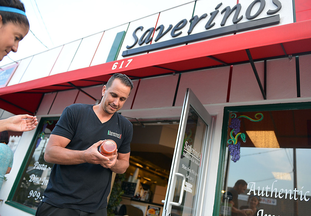 . David Saverino outside his Redlands\' restaurant, with his wife Veronica, after he returned from the bottling process in Newport Beach Thursday May 8, 2014 with his first batch of bottled sauces.  Following the successful launch of Saverino\'s Italian Deli and Market in Redlands nearly two years ago, David Saverino is bottling the flavor of his business with the introduction of four separate sauces. In addition to selling the sauces at his deli, Saverino hopes to see his product on the shelves of local markets. (Photo by Rick Sforza/Redlands Daily Facts)
