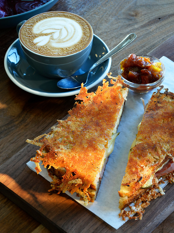 . The ham and Swiss Frico sandwich at Stowaway, a  new location for coffee and dining which  has come to Denver\'s RiNo neighborhood. Stowaway was  photographed on Thursday, March 10, 2016. The sandwich features Niman Ranch ham, house pickle, Emmental Swiss, dijon mustard on Babette\'s pullman crisped with montasio.  A cappuccino sits at the ready in the background.  (Photo by Cyrus McCrimmon/ The Denver Post)