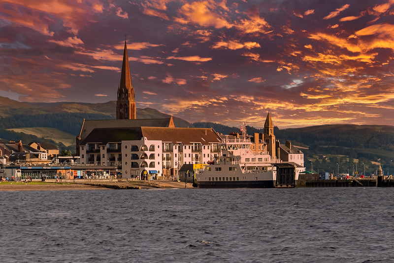 Largs Pier and the Cal-Mac Ferry fronting the Largs Town Centre in Scotland as the sun goes down in the west